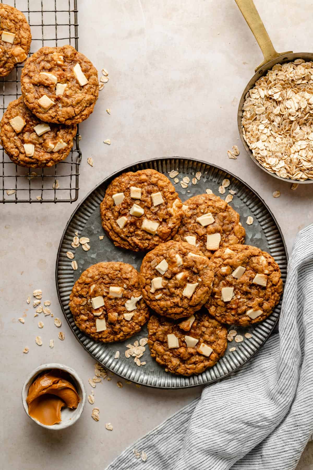Biscoff and white chocolate chip oatmeal cookies on a plate and cooling rack, with oats and biscoff in dishes nearby