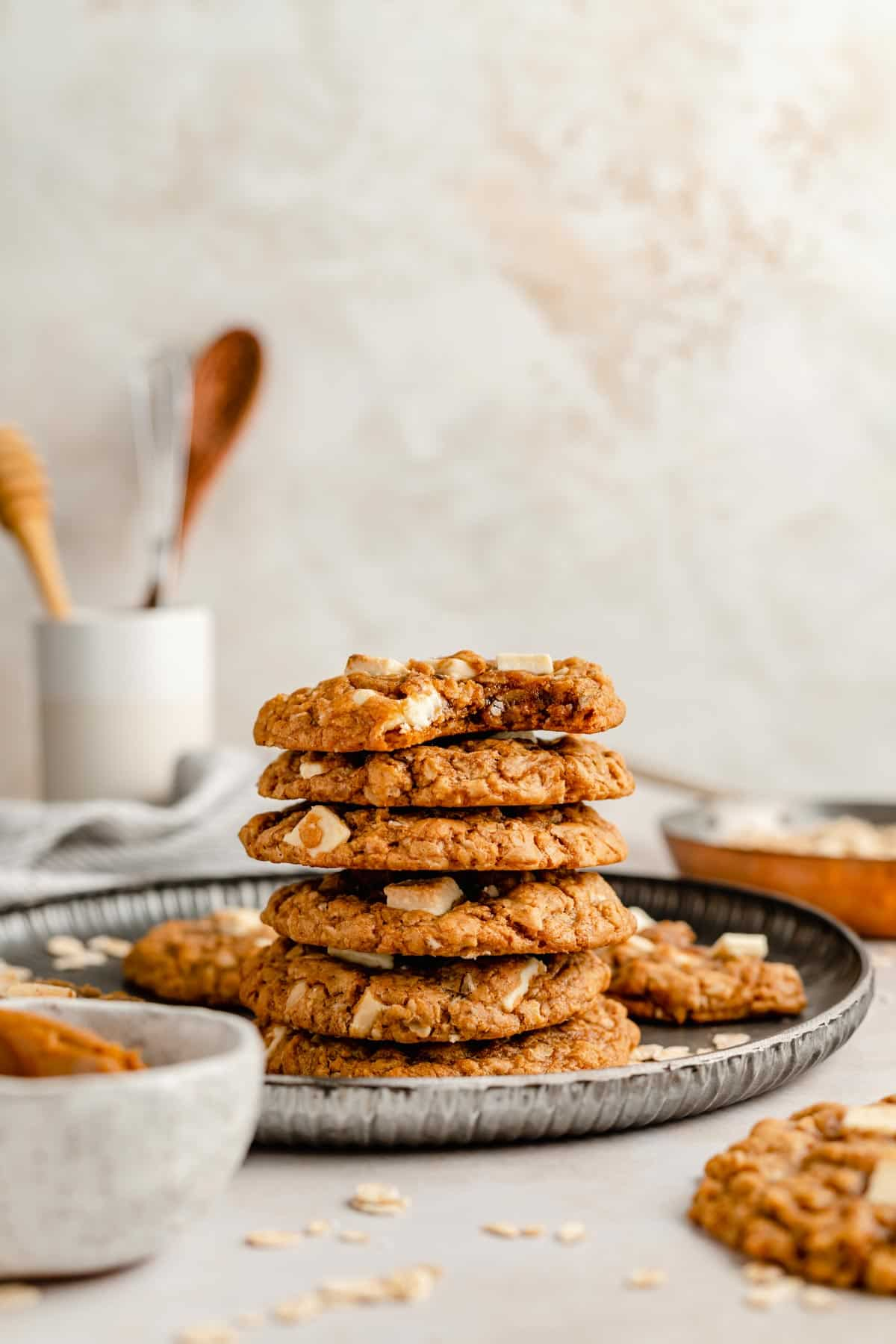 Stack of biscoff white chocolate chip oatmeal cookies on a plate with some utensils in a jar behind
