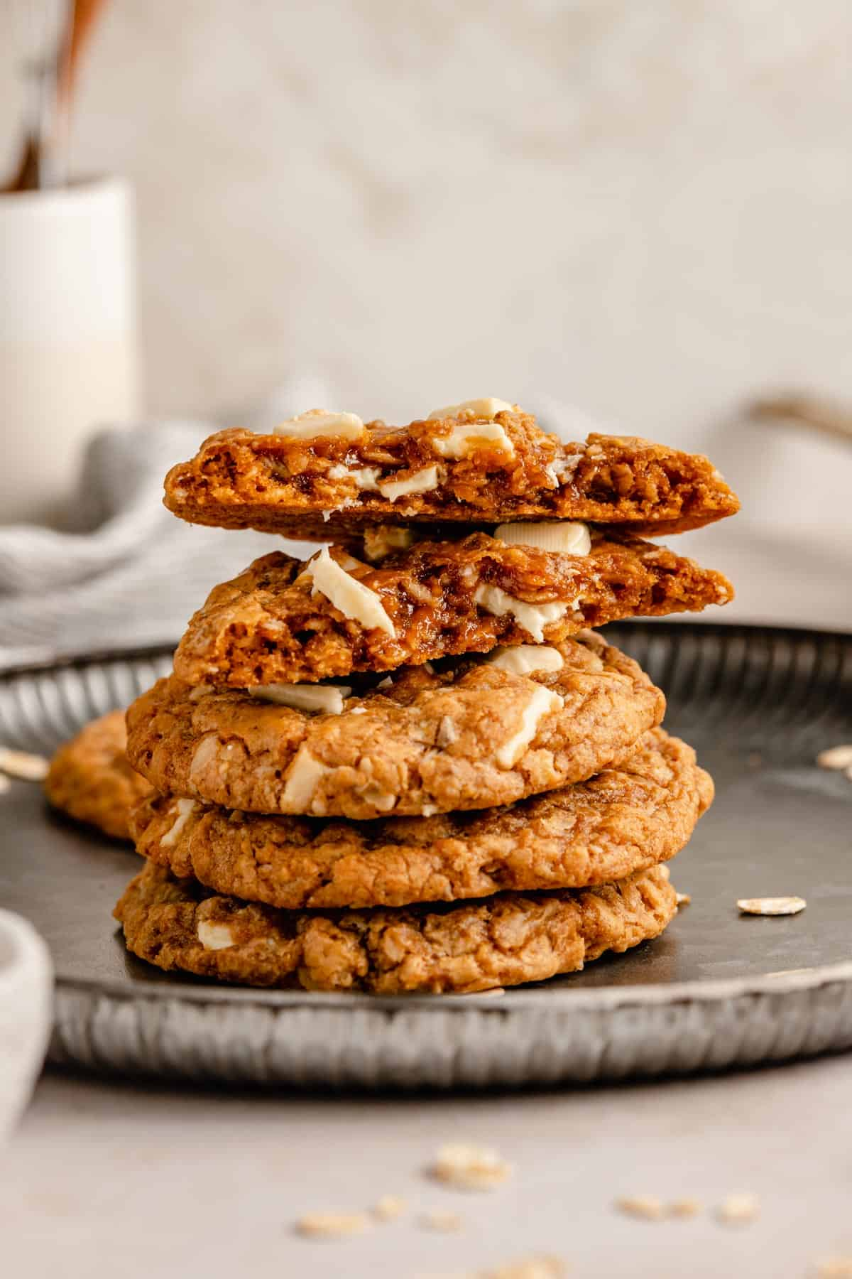 Biscoff cookies in a stack on a plate with one broken in half showing gooey insides
