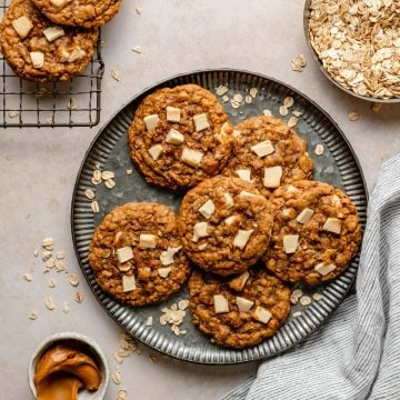 Oatmeal cookies on a plate with rolled oats and biscoff in dishes