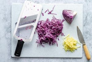 Red Cabbage and ginger sliced on a board with a mandolin on the side