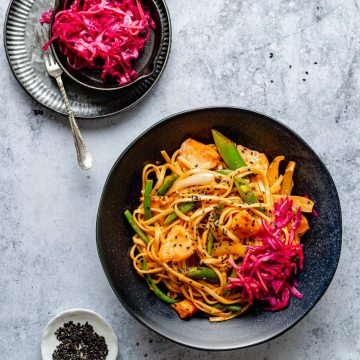 gochujang noodles with salmon in a bowl with cabbage on the top