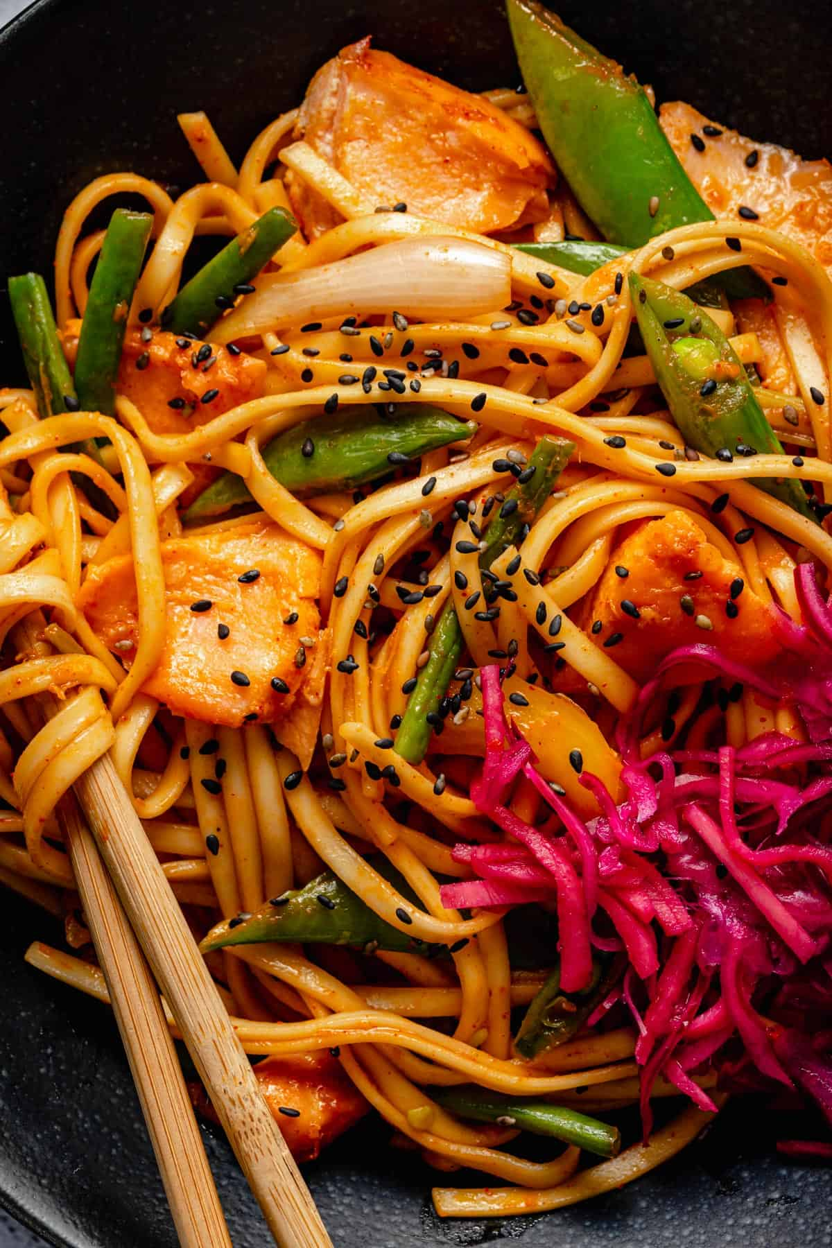 close up of noodles and salmon in a bowl with chopsticks and pickle to the side