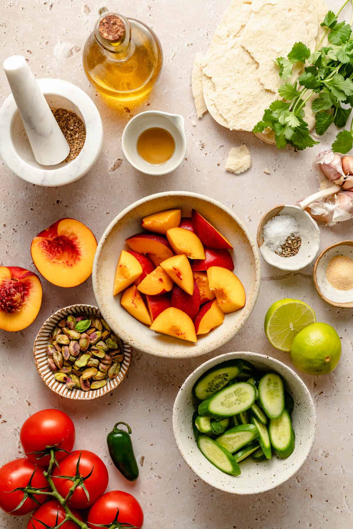 An array of ingredients in bowls, including nectarines, cucumbers, tomatoes, pistachios and seasonings