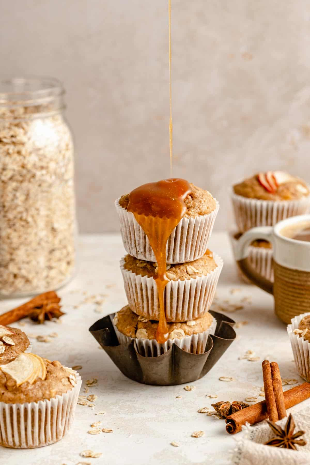 Stack of apple oatmeal muffins with caramel being poured over the top