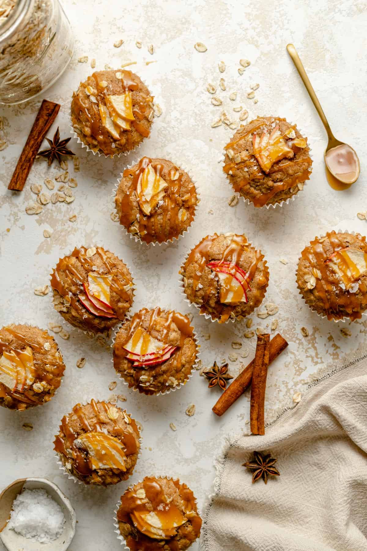 Array of apple oatmeal muffins with caramel drizzled on top and spices nearby