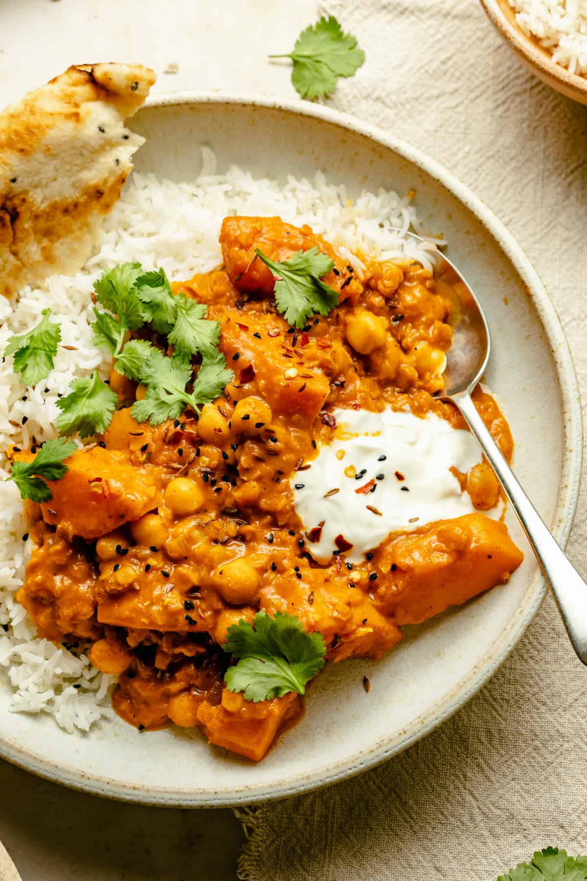 Butternut squash curry in a bowl served on basmati rice with yoghurt and naan.