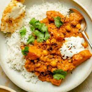Butternut squash curry served in a bowl on rice with yoghurt, naan and a spoon.