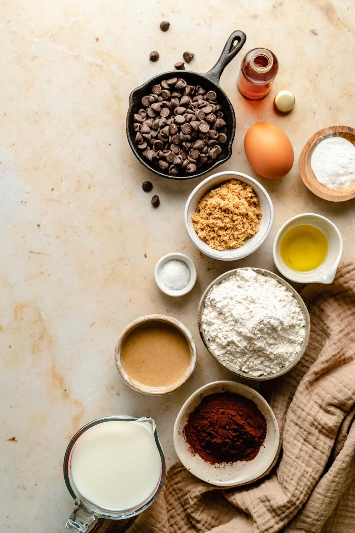 Array of ingredients for drop pancakes in various bowls including cocoa powder.