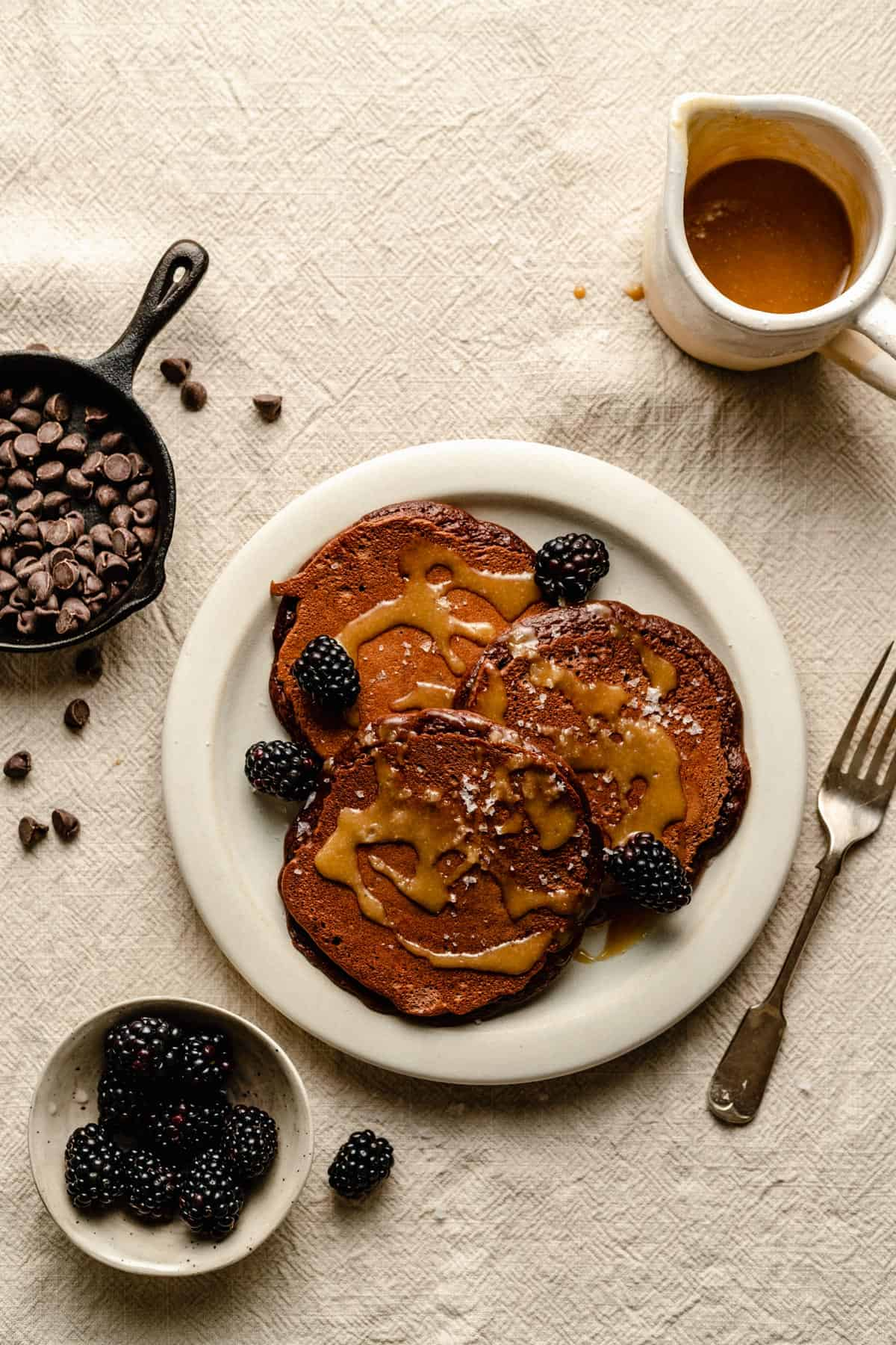 Breakfast setting of pancakes with blackberries and syrup topping and chocolate chips.