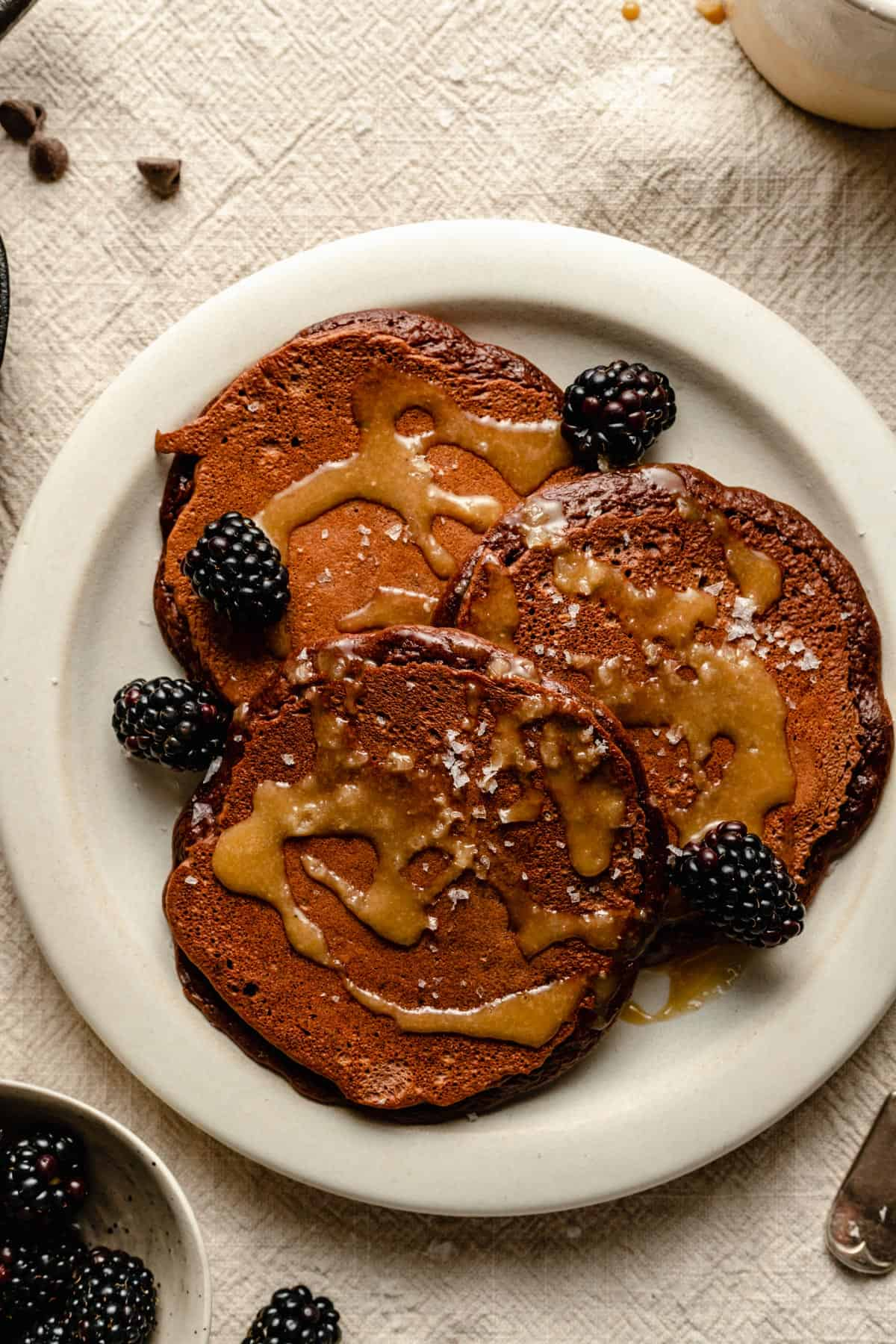 Pancakes topped with syrup, blackberries and flaky salt.
