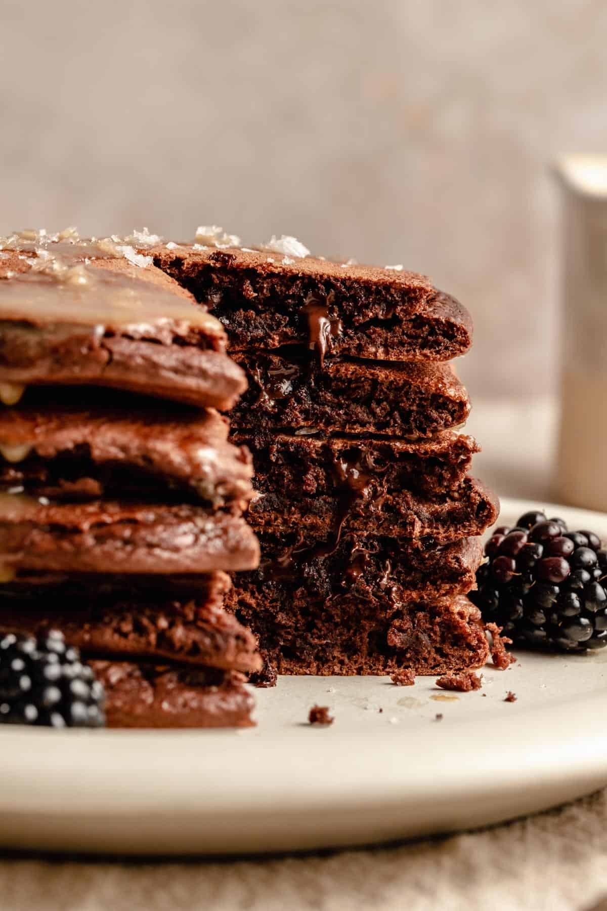A stack of double chocolate pancakes with a chunk cut out and chocolate chips melting out.