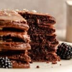 a stack of chocolate pancakes with a wedge cut out of it and melty chocolate chips.