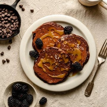 Chocolate pancakes on a plate drizzled with tahini maple syrup