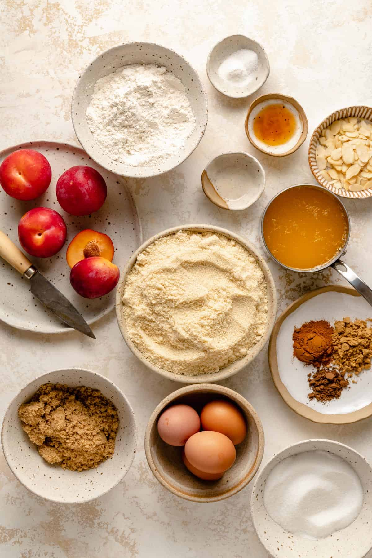 Ingredients required for the cake including almonds, plums, eggs, butter, spices and more