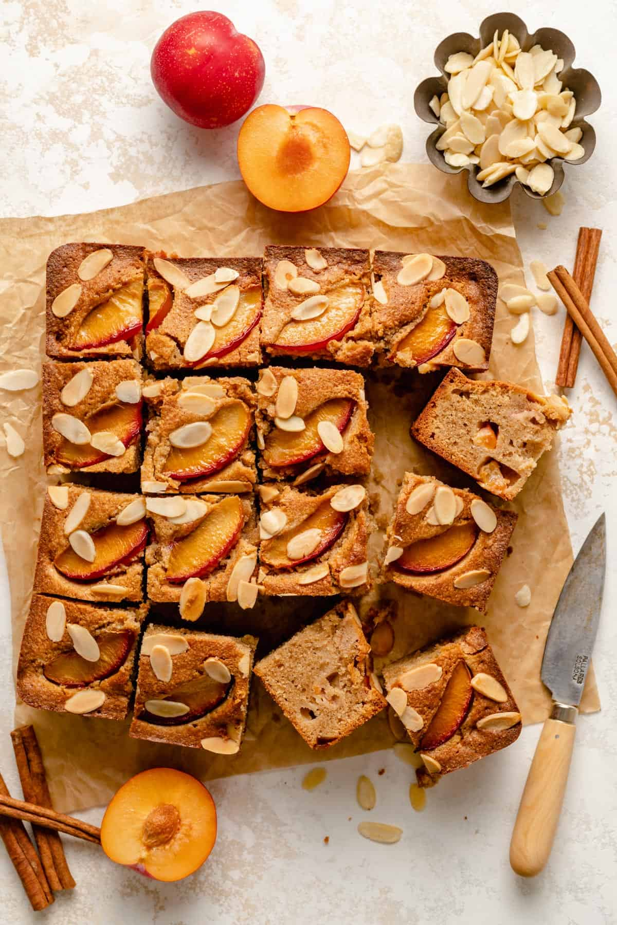 gluten free almond plum cake slices turned up in an array with a knife nearby