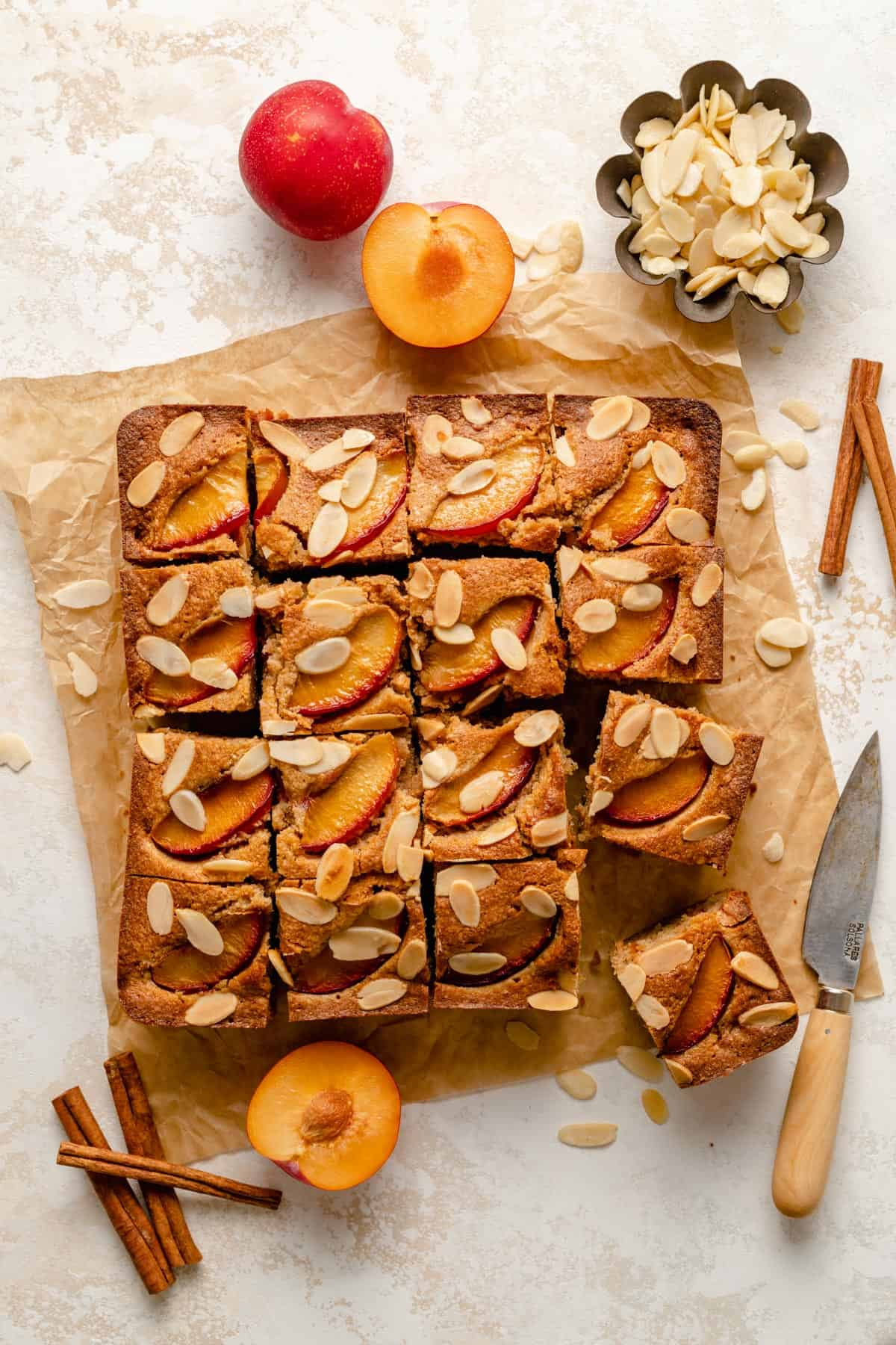 Plum and almond cake sliced into portions with plums, almonds and a knife around it