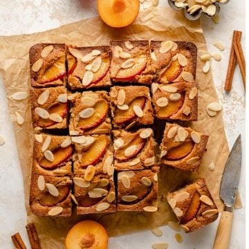 Plum and almond cake sliced up into portions with spices, plums and almonds around