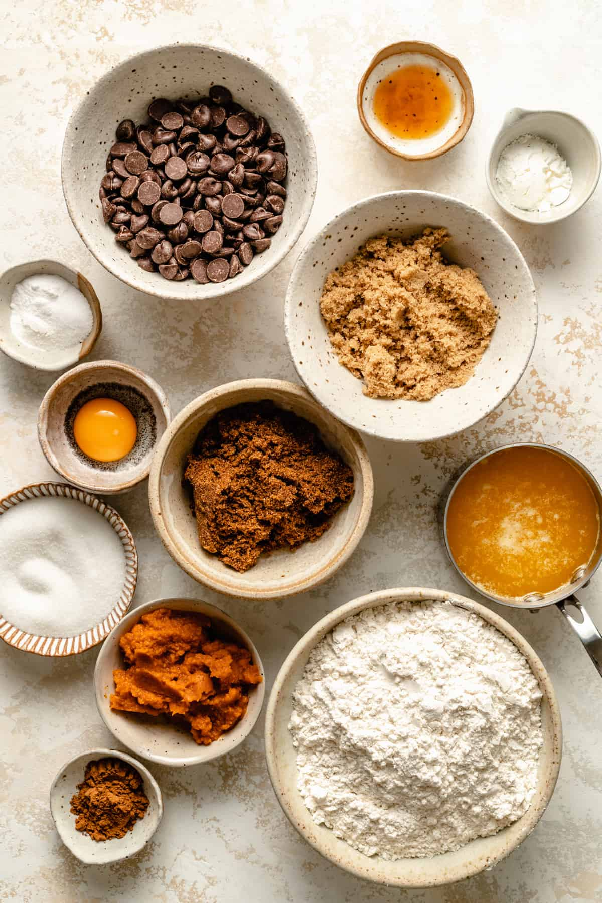 Ingredients in bowls: chocolate chips, pumpkin puree, melted butter, sugar, flour, baking powder & soda, pumpkin spice.