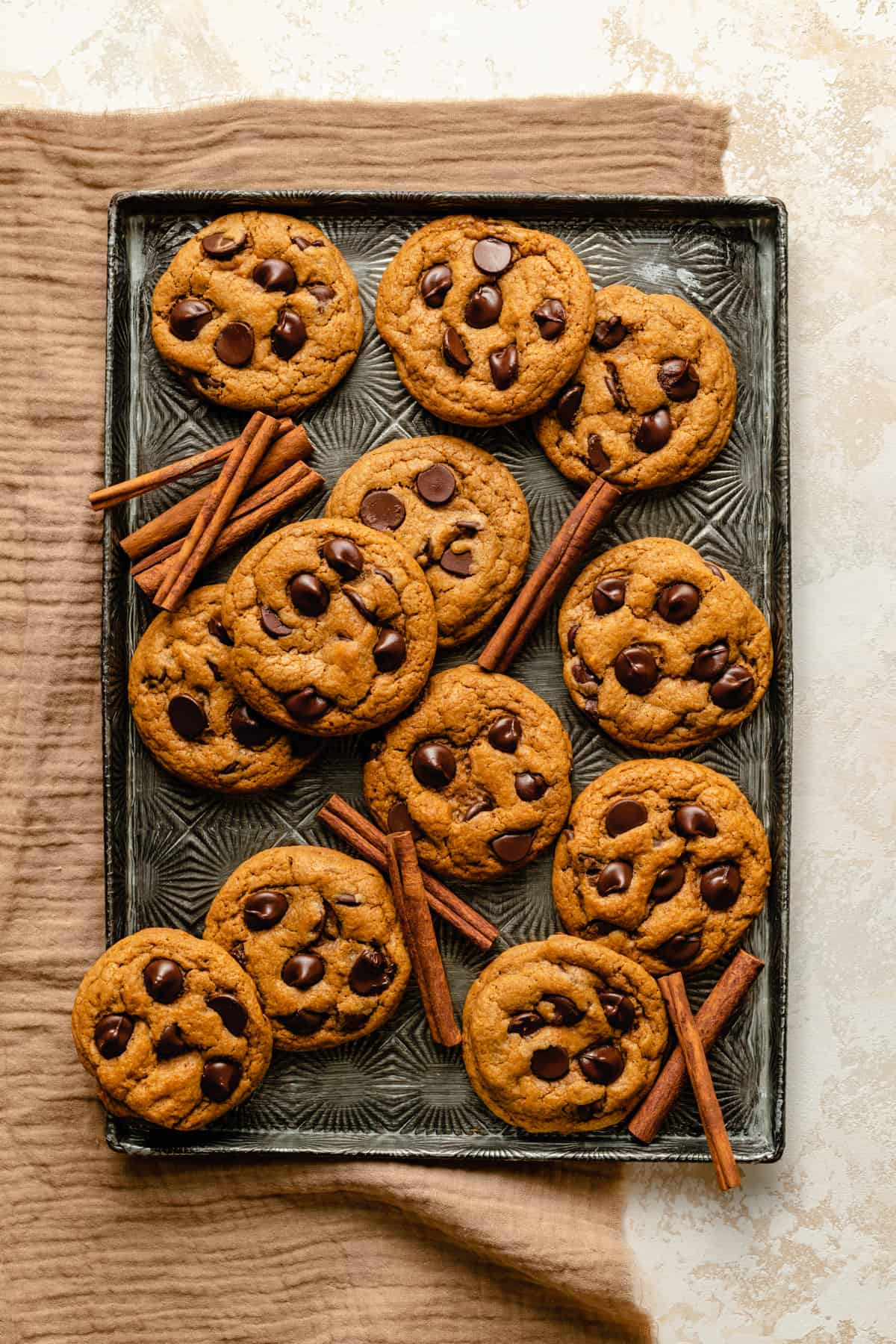 A tray of chewy cookies with cinnamon sticks scattered amongst them.