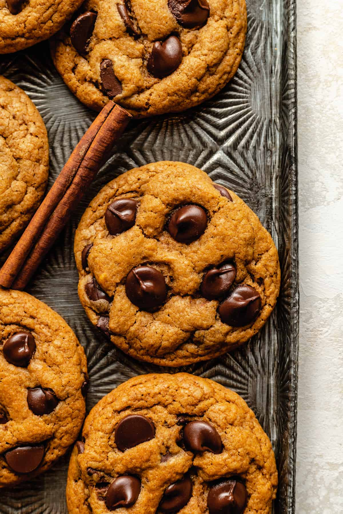A close up of a tray of cookies with cinnamon sticks around.