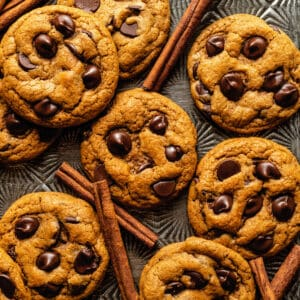 A tray of pumpkin chocolate chip cookies with cinnamon sticks scattered amongst them.