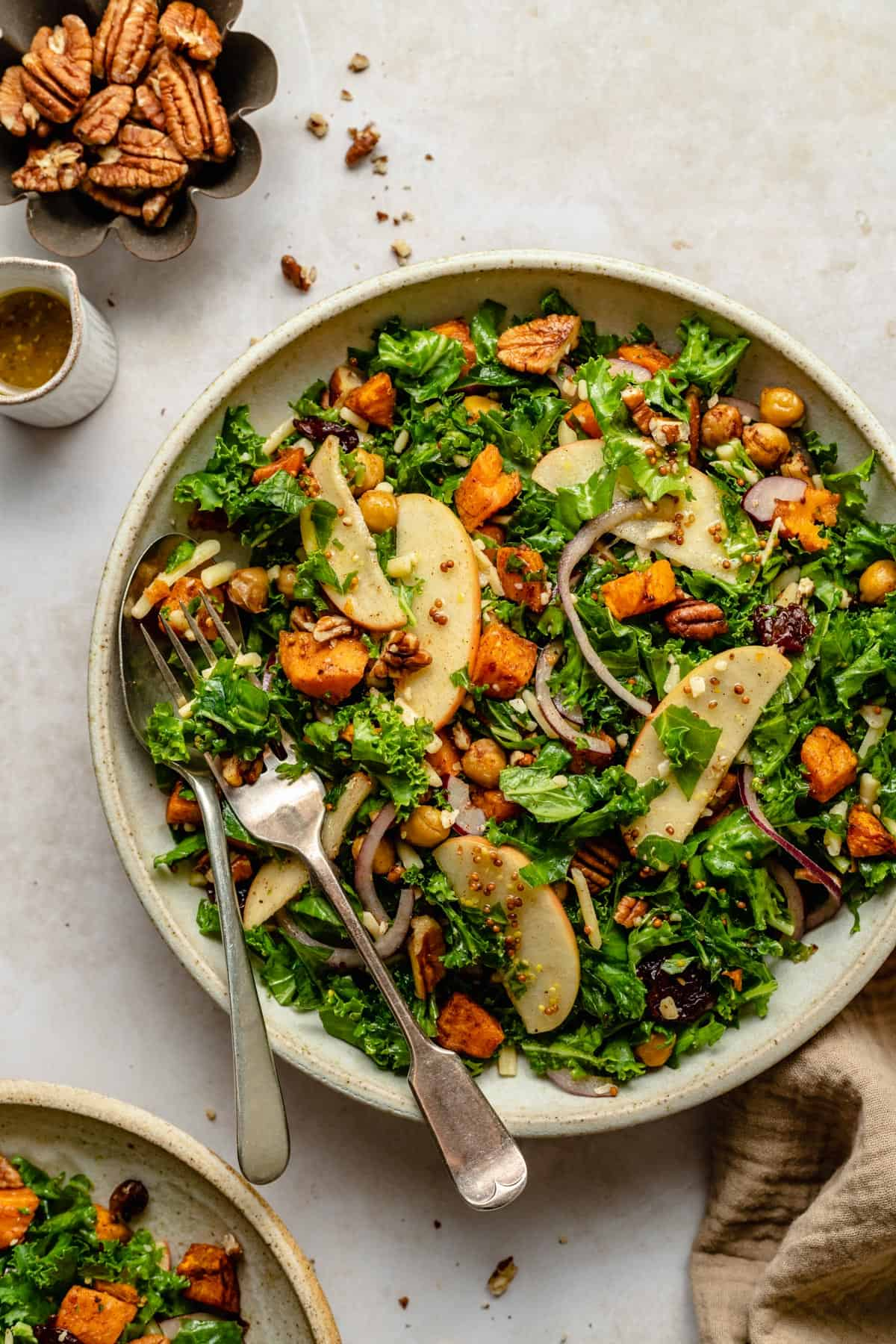 Warm sweet potato kale salad in a serving bowl with a spoon and fork and a jug of dressing
