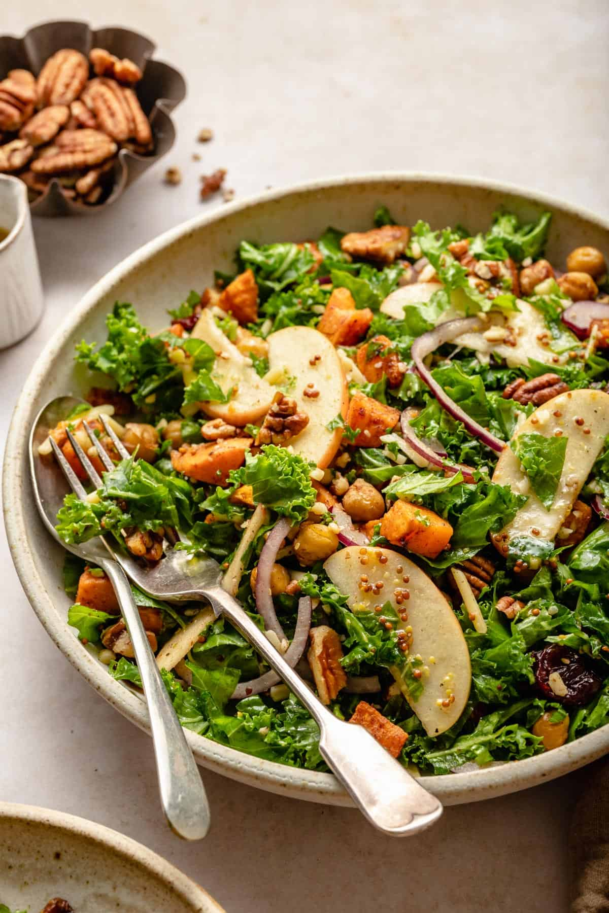 Kale salad with apples, chickpeas and   red onion with a spoon and fork in a bowl.