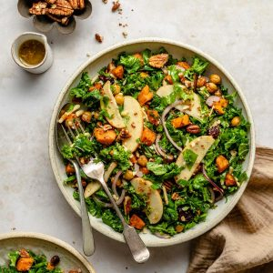 sweet potato kale salad with maple mustard dressing with spoon and fork to the side