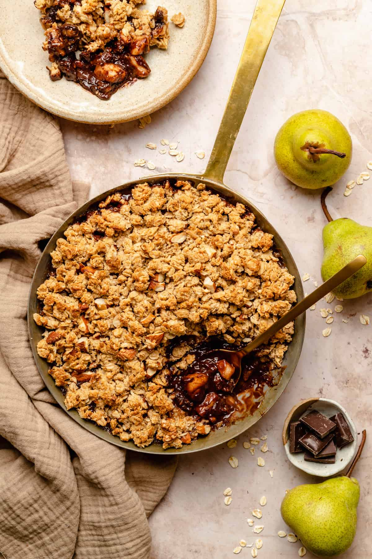 A copper pan with pear and chocolate crumble with a serving taken out of it and spoon showing the insides. Surrounded with pears, chocolate and oats.