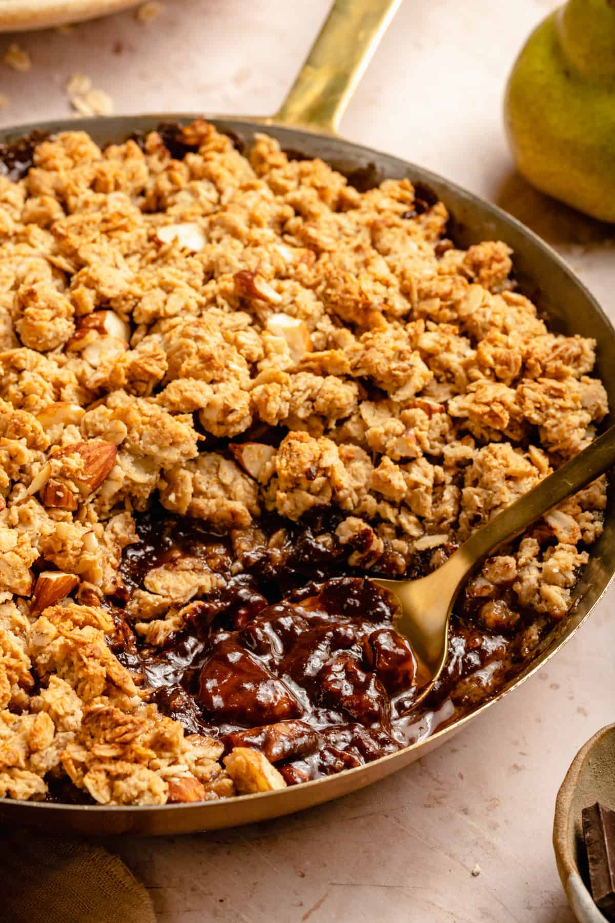 A spoon taking out a serving of crumble oozing with pears and chocolate with an oat and almond crumble topping.