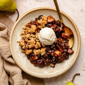 Pear and chocolate crumble served in a bowl with a spoon and a scoop of ice cream on top.