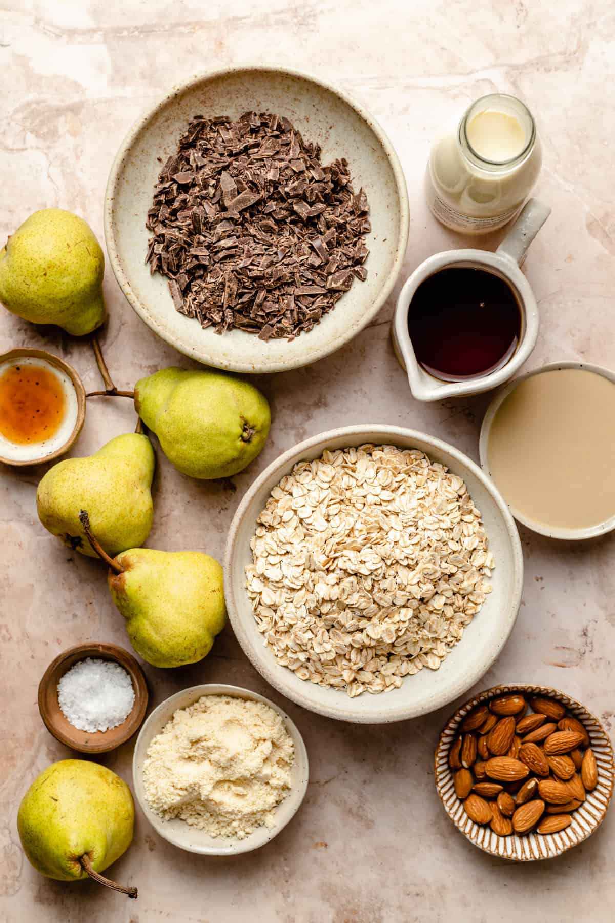 Ingredients in bowls: pears, chocolate, oats, tahini, maple syrup, almond flour, almonds, cream and vanilla extract.